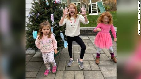 Brian Johnson's daughters pose for a picture with their pandemic Christmas tree.