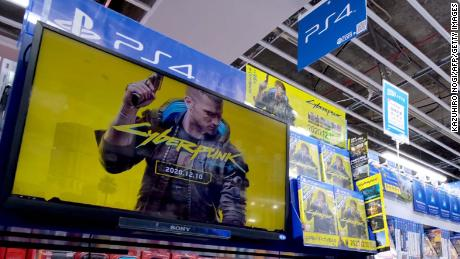"A screen shows a promotional video for ""Cyberpunk 2077"" in a store in Tokyo. Physical copies are still being sold."