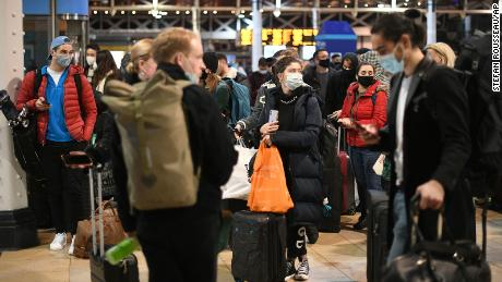 People wait on the concourse at Paddington Station in London after the announcement that the capital would soon move into Tier 4 Covid-19.