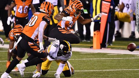 Vonn Bell forces a fumble by JuJu Smith-Schuster during the first quarter in their game.