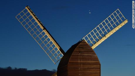 Jupiter and Saturn are seen coming together in the sky over the sails of Brill Windmill in Brill, Engeland.