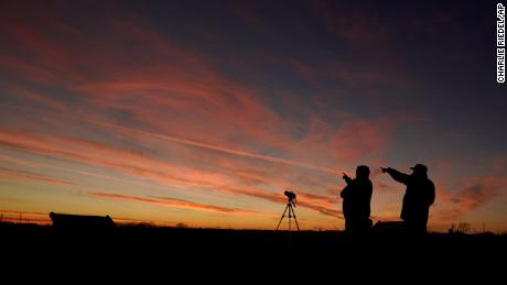 People are silhouetted against the sky at dusk as they watch the alignment Monday in Edgerton, Kansas.