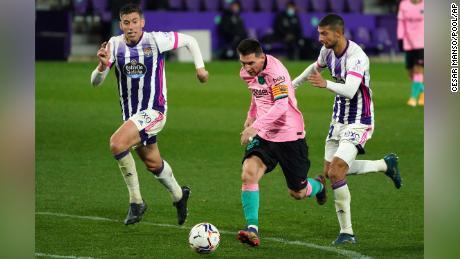 Messi (middle) runs past Real Valladolid's Ruben Alcaraz (right).