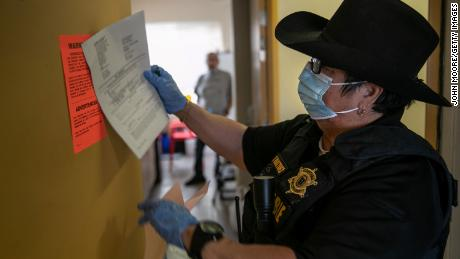 Maricopa County constable Darlene Martinez posts an eviction order for non-payment of rent on October 1 in Phoenix, Arizona. (Photo by John Moore/Getty Images)
