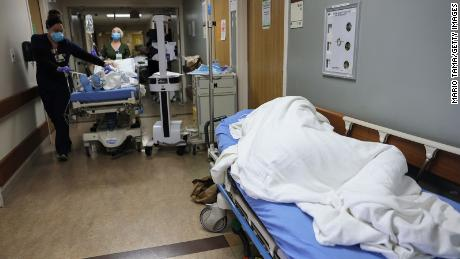 A patient lies on a stretcher in the hallway of the overloaded emergency room at Providence St. Mary Medical Center in Apple Valley, California, on December 23, 2020.