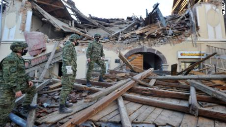 Soldiers inspect the destruction in Petrinja.