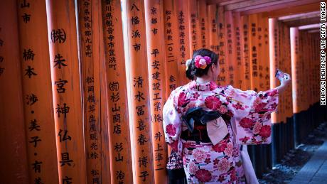 In this picture taken on December 9, 2018 tourists wearing kimono take selfies on the walking pass through the torii gates at Fushimi Inari Shrine in Kyoto. (Photo by Behrouz MEHRI / AFP)        (Photo credit should read BEHROUZ MEHRI/AFP via Getty Images)
