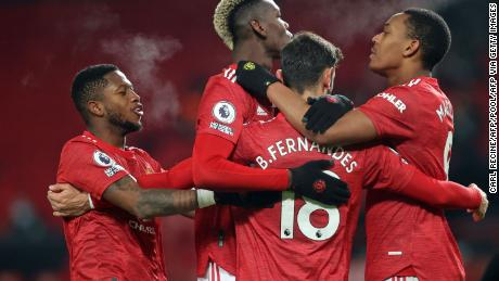 Manchester United's Portuguese midfielder Bruno Fernandes celebrates with teammates after putting his side 2-1 ahead from the penalty spot against Aston Villa on Friday, January 1.
