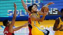 Curry drives to the basket between Portland Trail Blazers guard CJ McCollum and center Enes Kanter.
