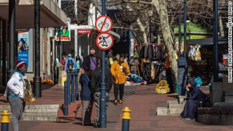 Pedestrians walk through an outdoor market area in Cape Town, South Africa, August 19.