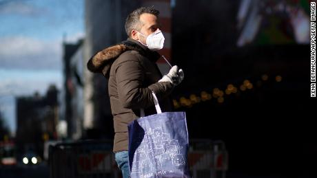 Wearing a mask in public helps protect the community from the spread of the coronavirus. A man wears a mask as he visits Times Square in New York December 10.