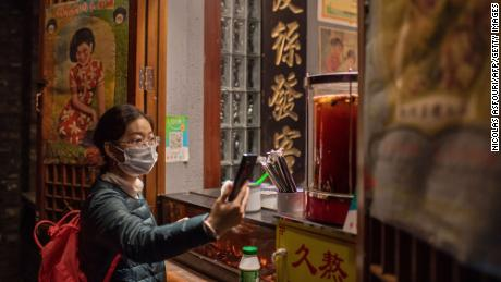 This picture taken in October shows a customer using Alipay to scan a QR payment code to make an electronic payment for a beverage at a shop in Beijing.