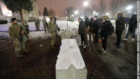 प्रदर्शनकारियों ने मंगलवार रात को केनोशा काउंटी कोर्टहाउस के पास नेशनल गार्ड सदस्यों का सामना किया।