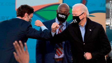 Democrats Jon Ossoff (left), Raphael Warnock (center) and US President-elect Joe Biden bump elbows on stage during a rally in Atlanta on January 4, 2021.