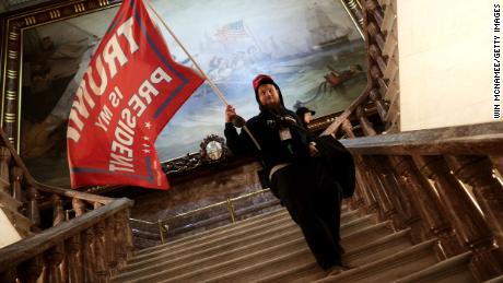 A rioter holds a Trump flag near the Senate chamber.
