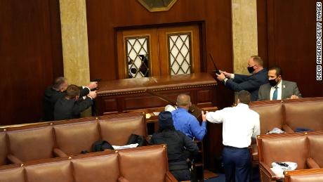 Law enforcement officers point their guns at a door that was vandalized in the House Chamber.