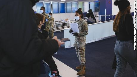 A member of the New York Army National Guard hands out health forms to travelers wearing protective masks at LaGuardia Airport on December 24.