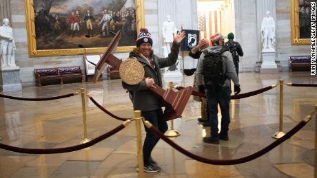 ट्रंप समर्थक एक समर्थक अमेरिकी कैपिटल बिल्डिंग के रोटुंडा के माध्यम से हाउस नैन्सी पेलोसी के अमेरिकी अध्यक्ष का व्याख्यान करता है।