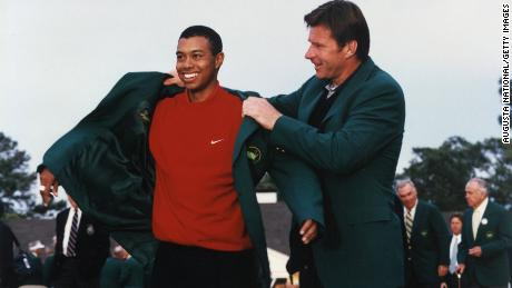 Woods puts on tthe Green Jacket with the help of Nick Faldo at the 1997 Masters presentation ceremony.