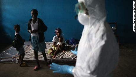 A Liberian health worker speaks with families in a classroom being used as an Ebola isolation ward on August 15, 2014 in Monrovia, Liberia.