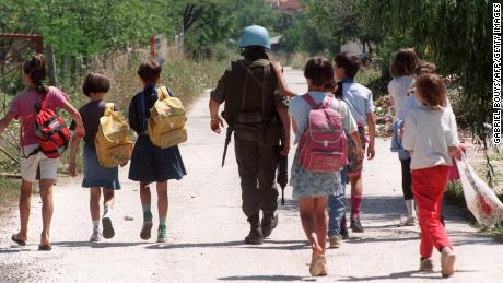 A United Nations Protection Force French soldier escorts a group of children after they left their school in a Sarajevo neighborhood a few hundred meters from the front line on August 14, 1993.