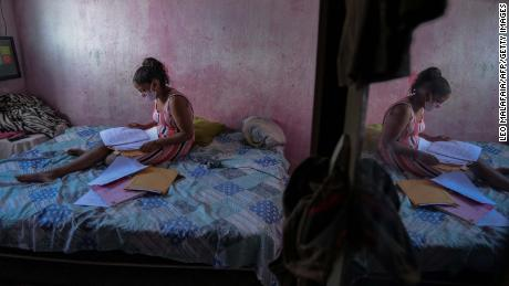 Student Gloria Dayane prepares to do her homework on a printout version of a textbook in Camaragibe, Pernambuco state, Brasilië, on July 25, 2020.