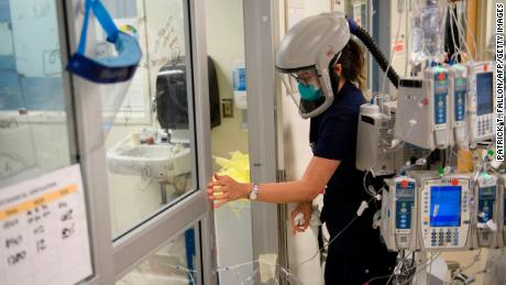 A nurse wearing personal protective equipment (PPE), including a personal air purifying respirator (PAPR), closes a door to a patient's room in a Covid-19 intensive care unit at Martin Luther King Jr. (MLK) Community Hospital on January 6, in the Willowbrook neighborhood of Los Angeles.