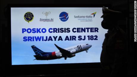 A security personnel stands in front of a sign for a crisis centre for Sriwijaya Air flight SJY182 at the Soekarno-Hatta international airport in Tangerang near Jakarta on January 9, 2021.