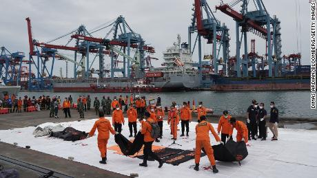 Search and rescue team members carry bags containing remains of victims recovered from the Sriwijaya Air SJ 182 crash site on the dockside at Tanjung Priok Port in Jakarta, Indonesia, on Sunday.