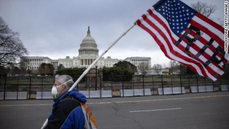A protester walks by as the American flag flies at half-staff at the US Capitol on January 8, 2021, in Washington.