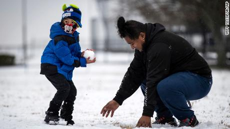 Jonathan Godoy, 5, looks for a target as Elias Gonzales makes a new snowball Sunday near Fort Worth.