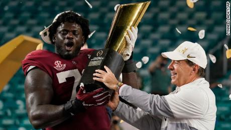 Alabama head coach Nick Saban and offensive lineman Alex Leatherwood hold the trophy after their win against Ohio State.
