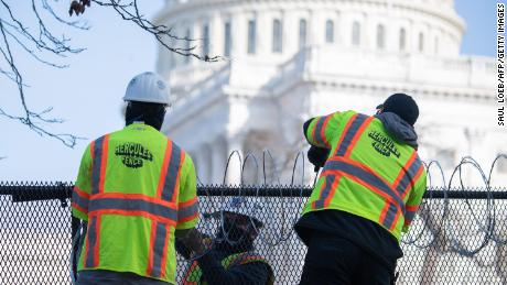 Barbed wire is installed on the top of a security fence surrounding the Capitol.