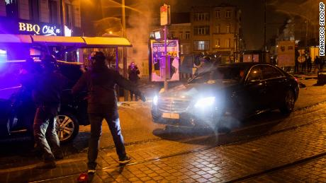 The escorted official car of Belgium's King Philippe makes a turn to avoid protestors.