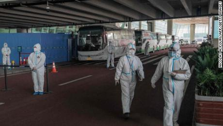 Health workers stand next to buses at a cordoned-off section, where arriving travellers are to be taken into quarantine, at the internatinoal airport in Wuhan, China on January 14, 2021, following the arrival of a World Health Organization (WHO) team investigating the origins of the Covid-19 pandemic.