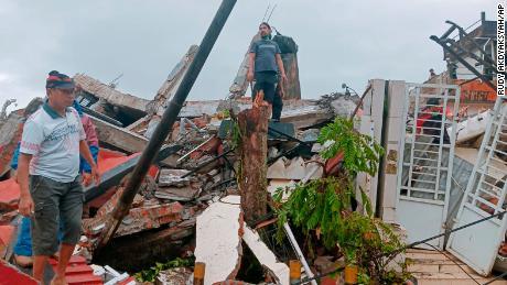 Residents inspect earthquake-damaged houses in Mamuju, West Sulawesi, Indonesia on Friday.