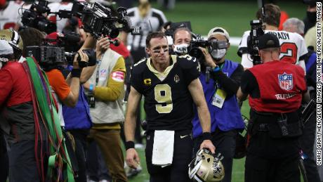 Brees walks off the field after defeat by Tampa Bay.