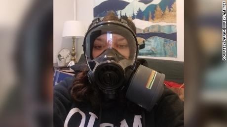 Los Angeles Times Congressional reporter Sarah Wire tries on the gas mask her newsroom sent to her home in preparation for Inauguration Day coverage.