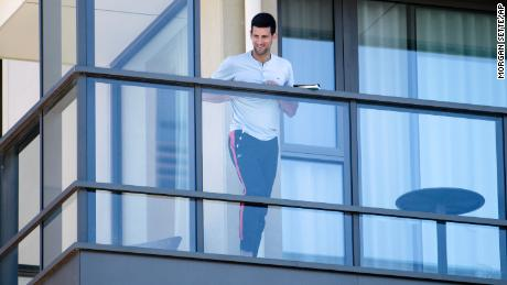 Serbia's Novak Djokovic stands on the balcony at his accommodation in Adelaide, Australia, on January 19, 2021.