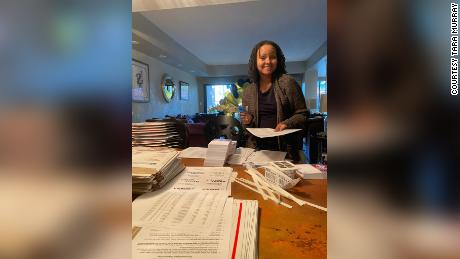 Human-rights lawyer Tara Murray founded Mamas for Momala, a group that mobilized voters in battleground states to support the Biden-Harris presidential ticket. In this photo, Murray prepares packages of postcards her group sent to Georgia voters.
