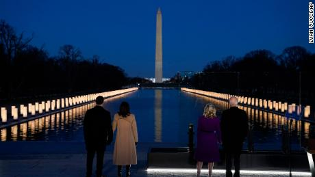 """With the Washington Monument in the background, President-elect Joe Biden with his wife Jill Biden and Vice President-elect Kamala Harris with her husband Doug Emhoff listen as Yolanda Adams sings """"Hallelujah"""" during a COVID-19 memorial, with lights placed around the Lincoln Memorial Reflecting Pool, Tuesday, Jan. 19, 2021, in Washington. (AP Photo/Evan Vucci)"""