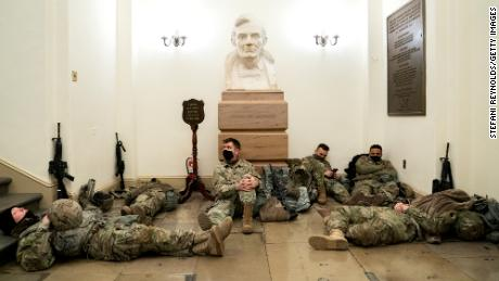 Members of the National Guard rest in the U.S. Capitol.