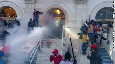 Police use tear gas as pro-Trump supporters riot and breach the building.
