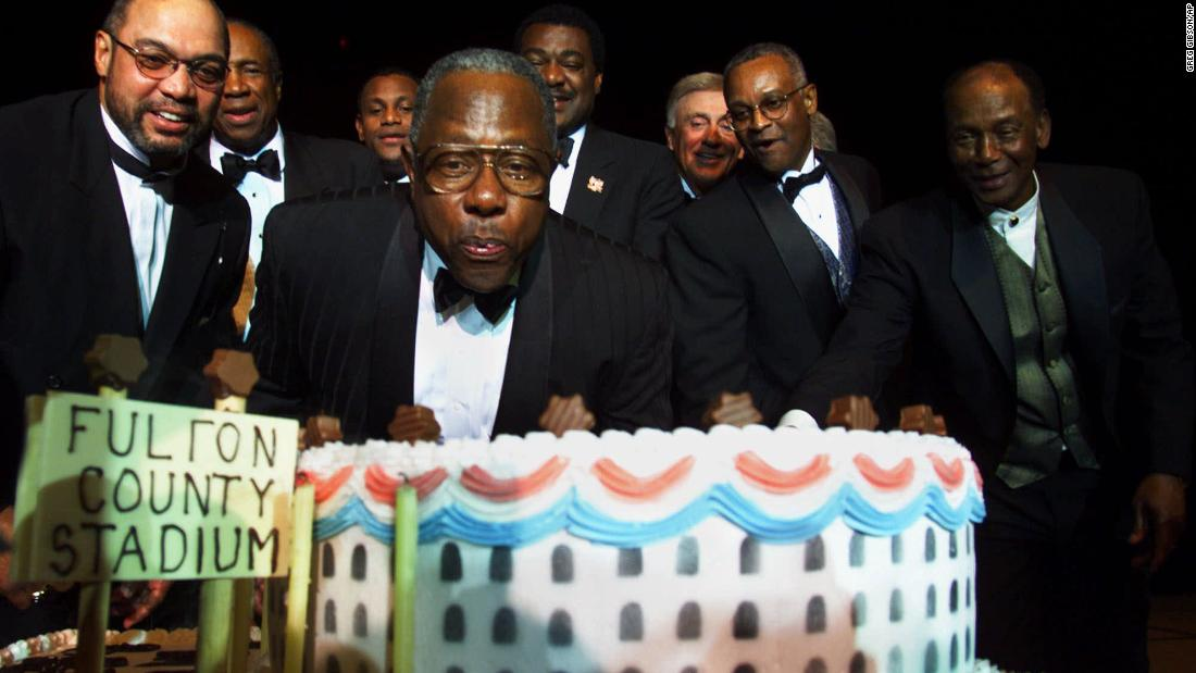 Aaron blows out candles for his 65th birthday in 1999. Behind him are many baseball greats: 왼쪽에서, Reggie Jackson, Frank Robinson, Sammy Sosa, Don Baylor, 필 니크로, Sonny Jackson and Ernie Banks.