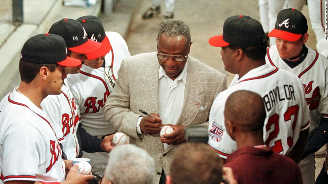 Aaron signs autographs for some of the Atlanta Braves in 1999.