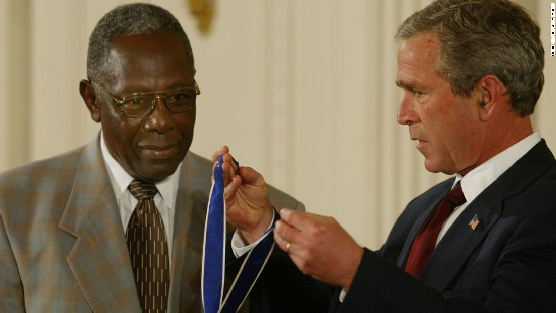 "总统乔治·W. Bush presents Aaron with the Presidential Medal of Freedom in 2002. ""By steadily pursuing his calling in the face of unreasoning hatred, Hank Aaron has proven himself a great human being, as well as a great athlete,&报价; Bush said during the ceremony."