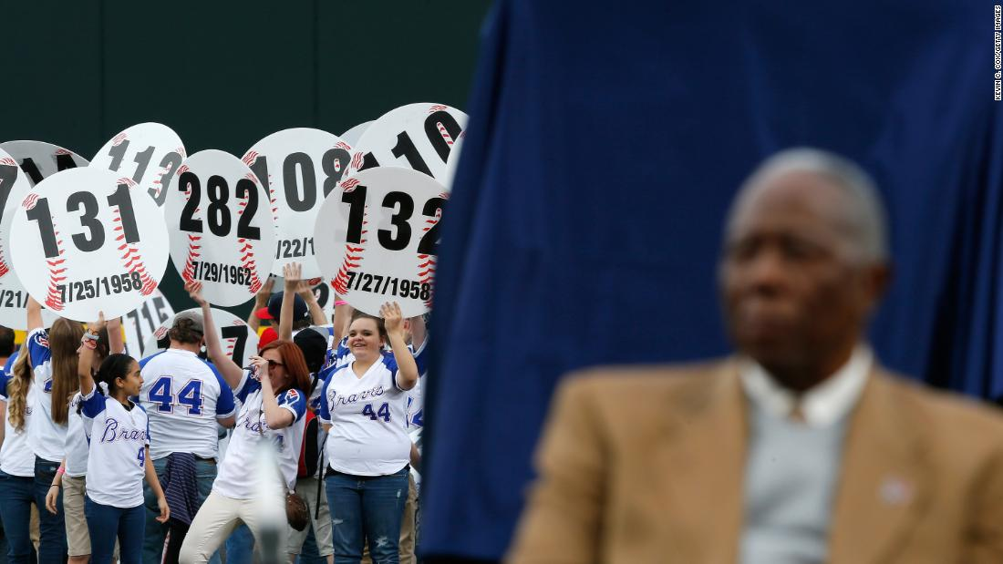 Atlanta fans hold up signs in 2014 that show every home run Aaron hit. He was being honored on the 40th anniversary of his 715th home run.