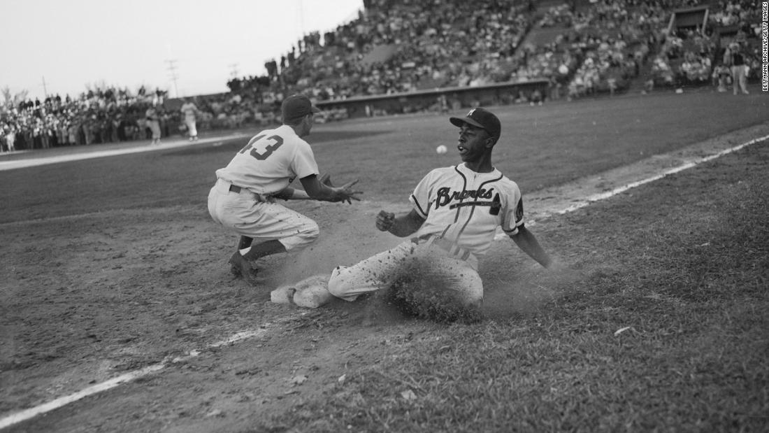 Aaron slides back to third base during an exhibition game in 1954. Aaron's career began in the Negro leagues before he broke into the majors with the Milwaukee Braves.