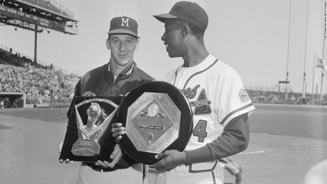 Aaron holds his MVP award with Braves pitcher Warren Spahn, who won the Cy Young Award that year.
