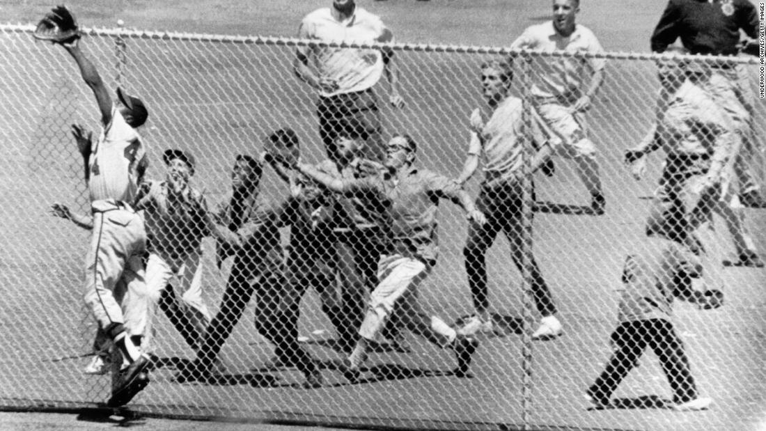 Fans rush to the fence at San Francisco's Candlestick Park as Aaron reaches for a catch in 1961.
